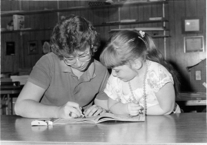 """Stephanie Winks, MHS Class of 1985, kept a newspaper deadline and still took time for with a coloring break with Lindsay. It was easy to find """"graphic design partners"""" in the publications room."""